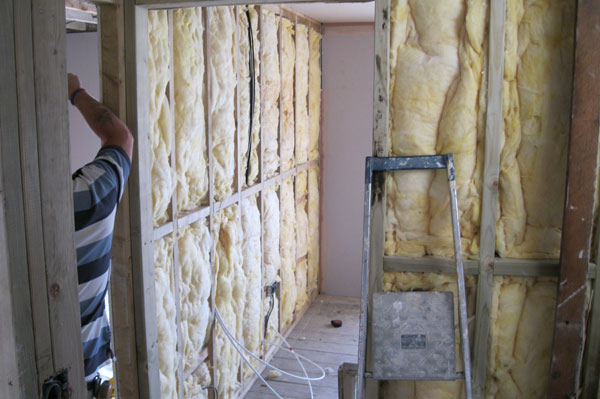 Installing sound proofing insulation by Dyfi Renovations Ltd